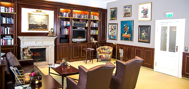 Das gemütliche Kaminzimmer im Gallery-Stil gehört zu den Lieblingsorten unser Gäste