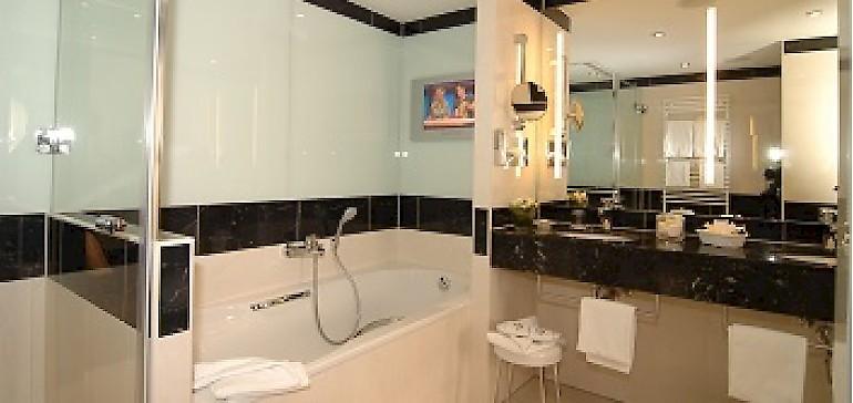 Großes Badezimmer mit Wanne, Dusche und TV