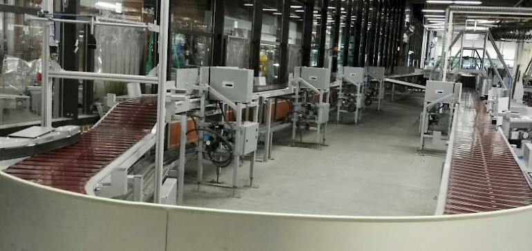 Laufband, welches Beilagen zu den Zeitungen sortiert