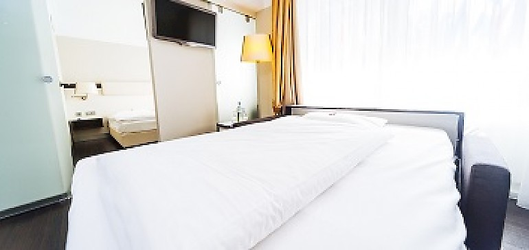 Aufgebaute Schlafcouch im Familienzimmer für bis zu zwei Kinder