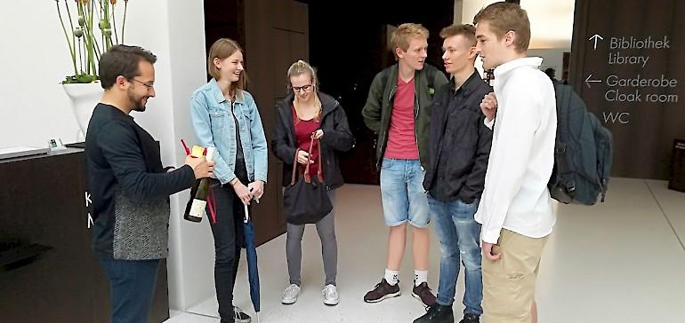 Die Azubis werden von einem Museumsmitarbeiter begrüßt, der sie durch die Ausstellung führt