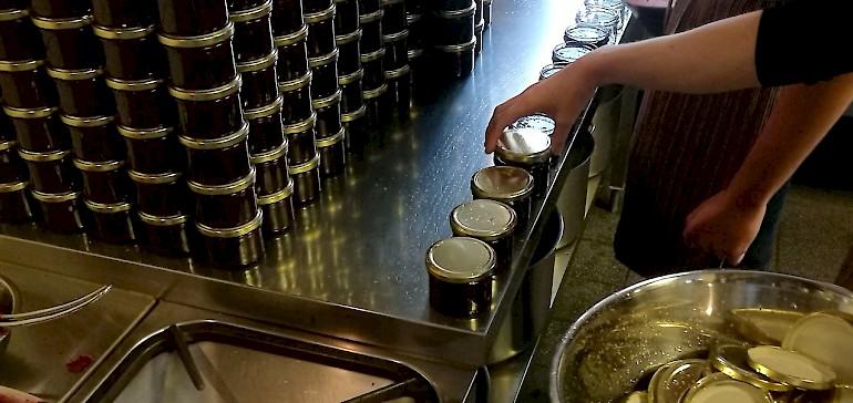 Mitarbeiter füllen die Marmelade in Gläser ab