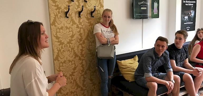 Eine Mitarbeiterin gibt den Teams eine Einführung zum Meistern des Escape Rooms