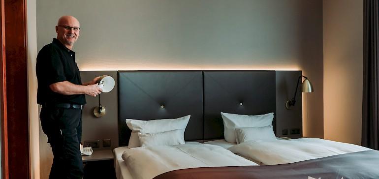 Ralf Klucken tauscht in allen Zimmer die Leuchtmittel gegen umweltfreundliche Alternativen aus.